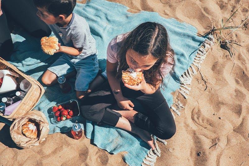 Två barn äter varsin bulle på stranden.
