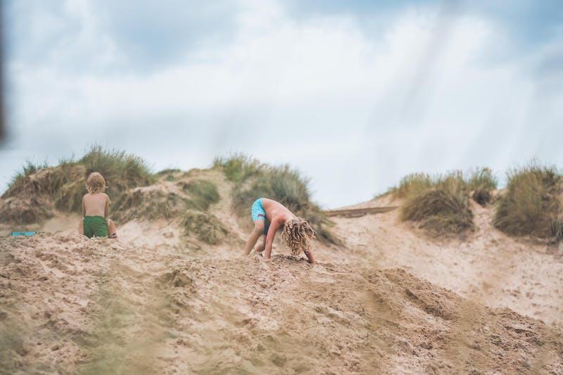 Två barn leker i sanddynorna.