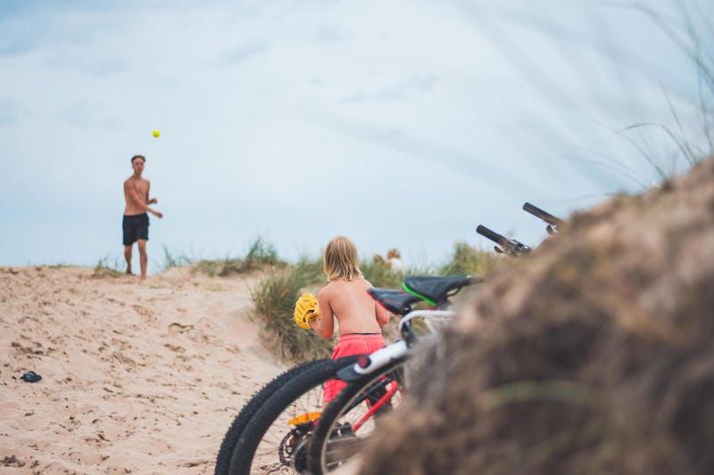 Två barn kastar boll till varandra på stranden.