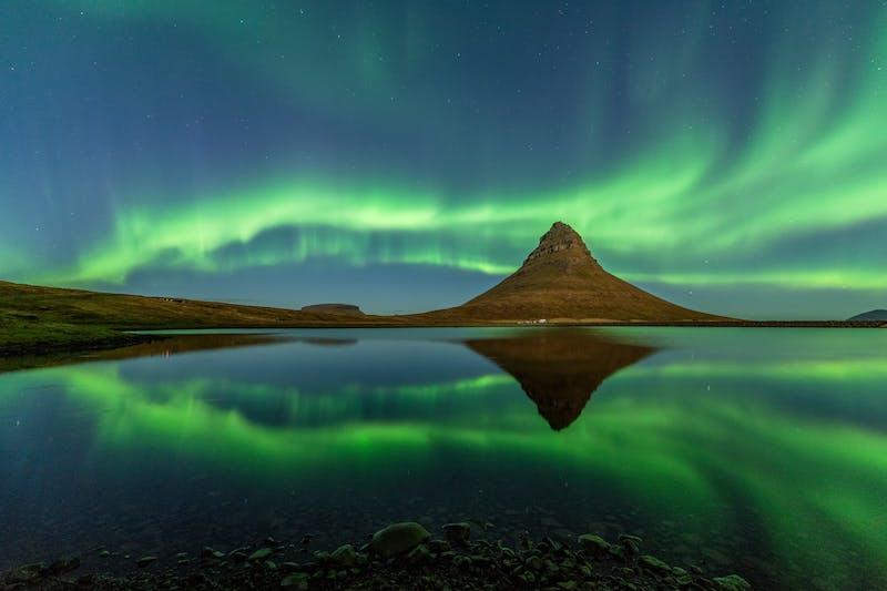 Northern lights dance above Kirkjufell mountain in Iceland