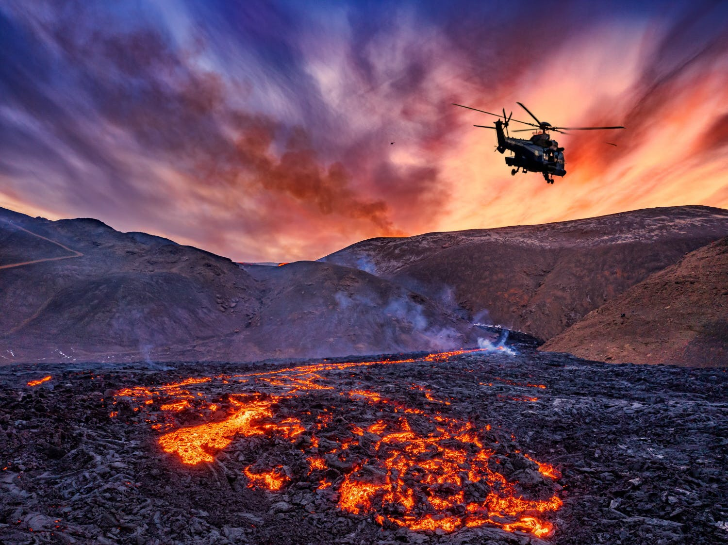 Helicopter flying over flowing lava