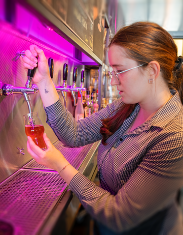 Young woman drawing a beer in an Icelandic bar