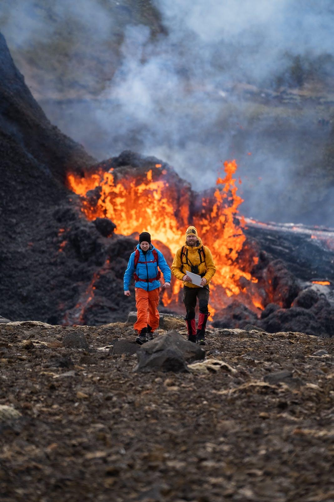 Two men walking past an erupting volcano