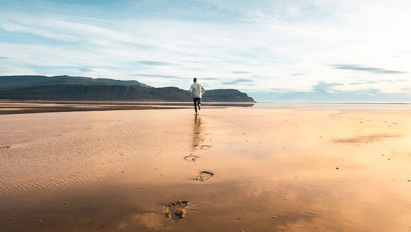 A man running on Raudisandur beach