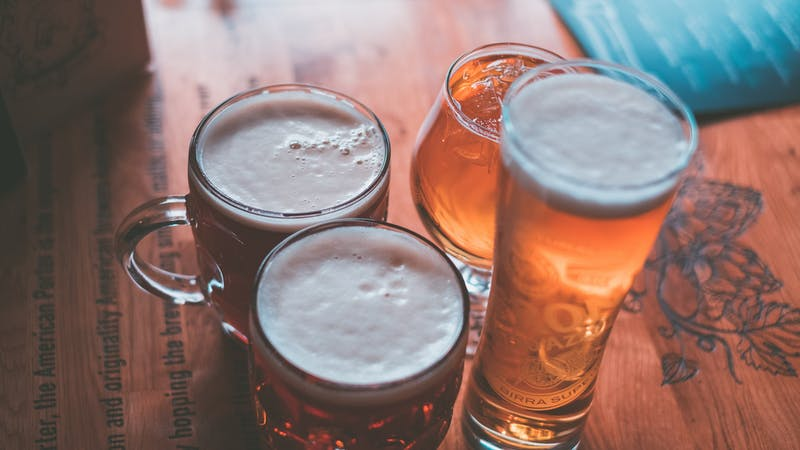 Four beer glasses on a wooden table