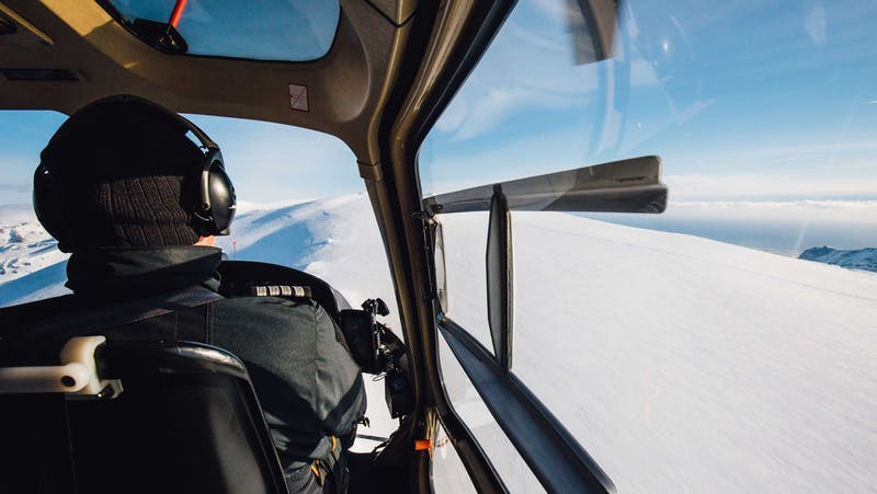 A pilot flying a helicopter iver snowy mountains