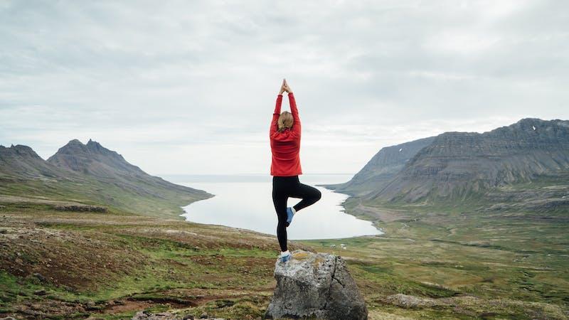 A woman doing a yoga pose outside