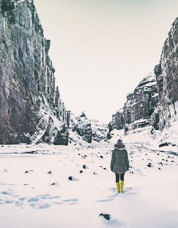 Woman walking in a ravine in snow