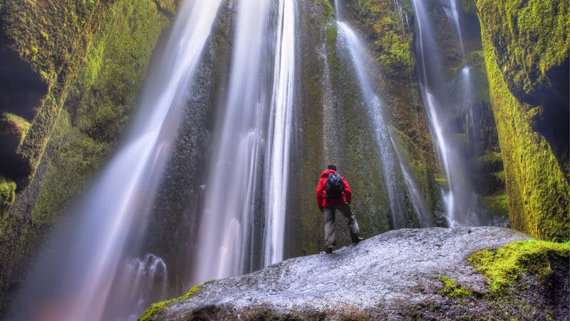 A man viewing Gljufrabui waterfall