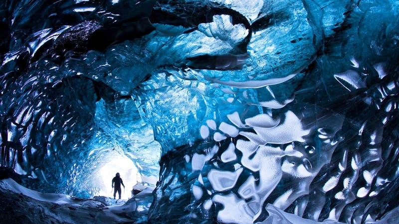 A man exploring a cave in Iceland