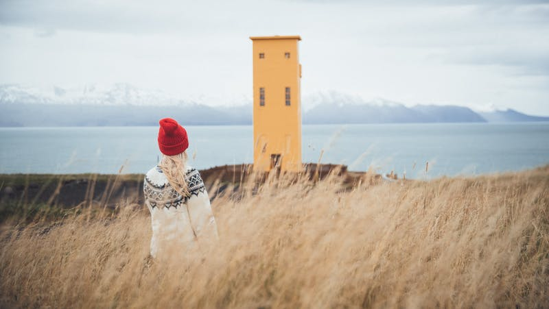 Young woman wearing a lopapeysa in front of a yellow lighthouse in North Iceland