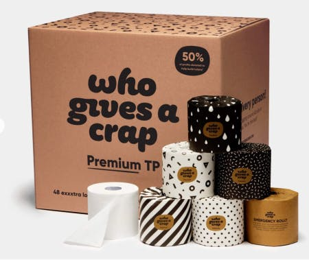 """Seven rolls of toilet paper sit in front of a cardboard box that says """"Who gives a crap."""""""
