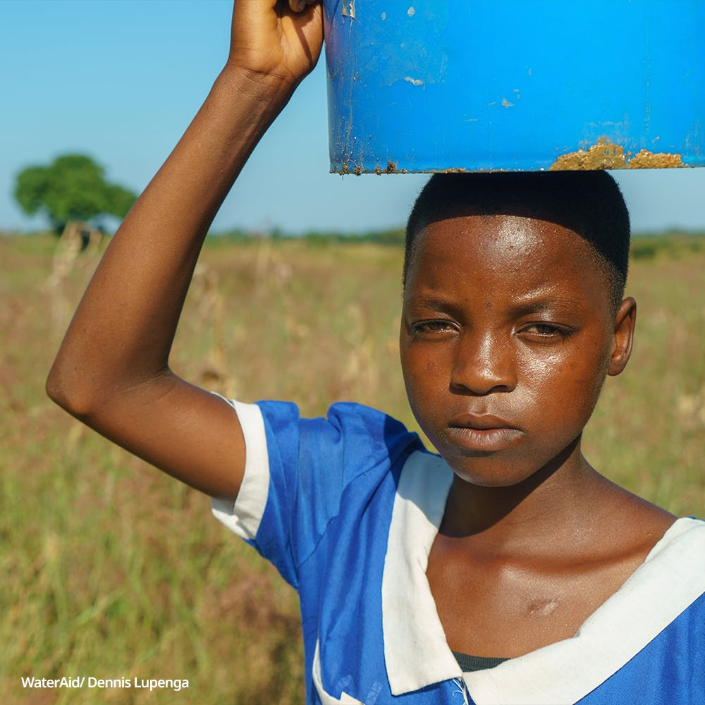 Tiyamike, 14, carries a bucket on her head, Malawi.