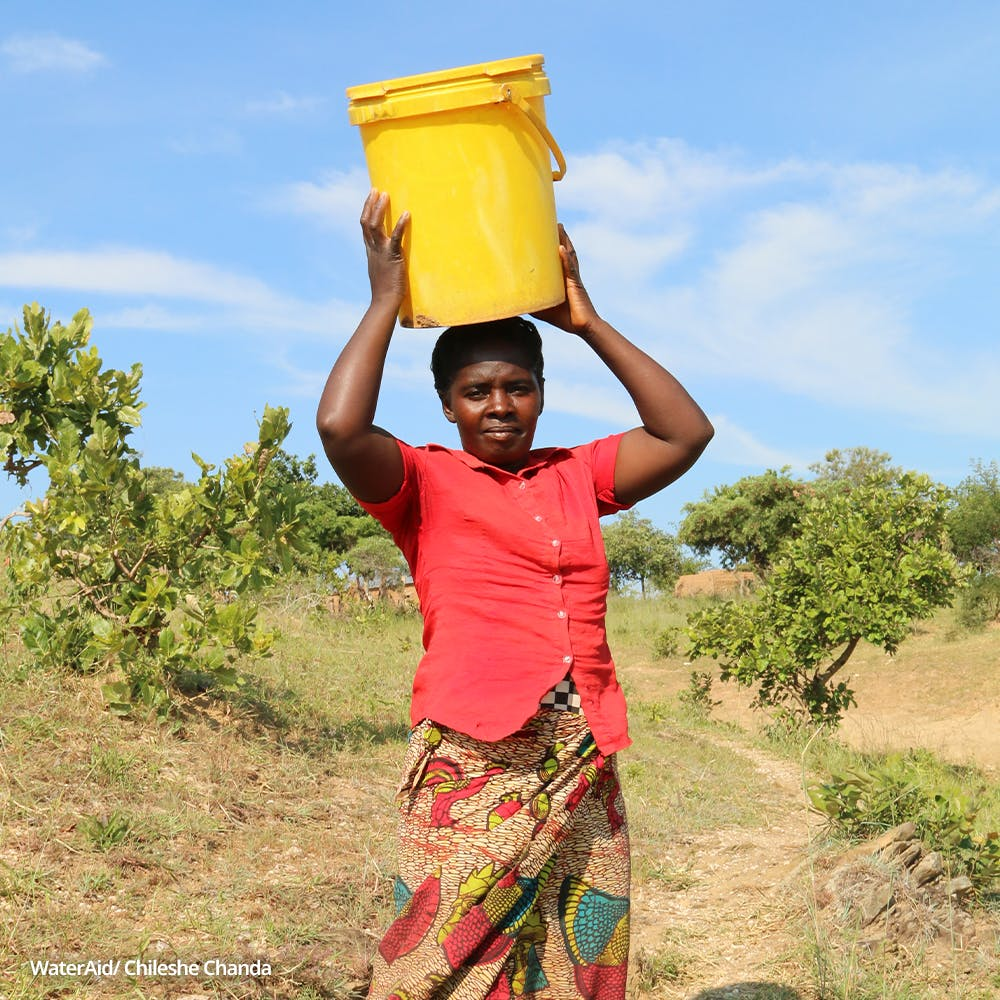 Majory, 37, carries a bucket on her head, Zambia.