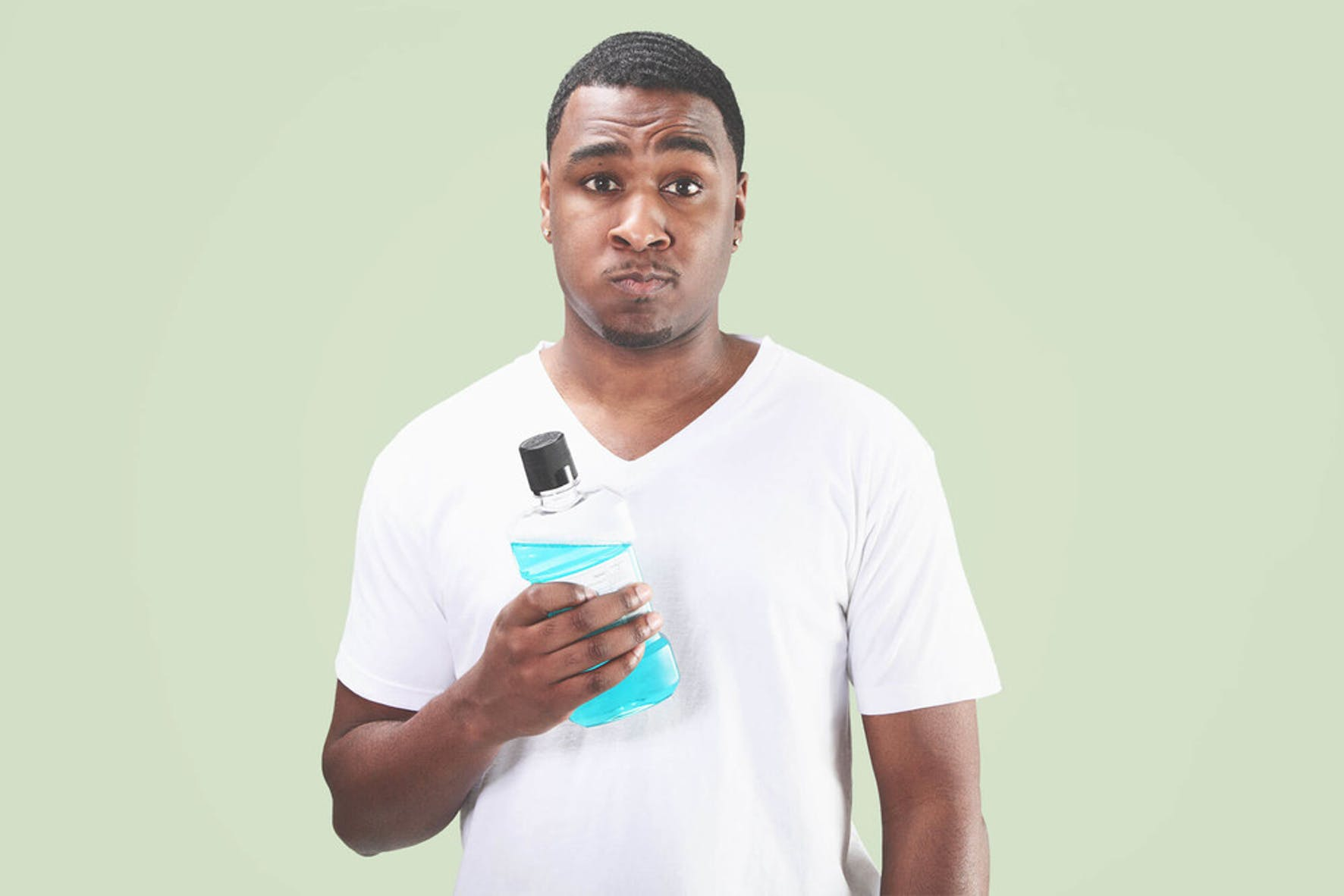 Guy shows mouthwash to maintain oral health