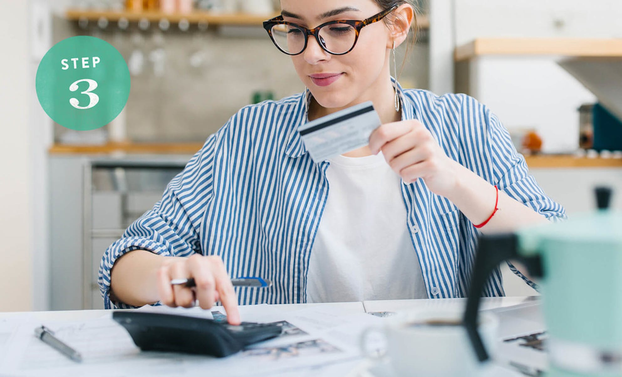 Typing on a calculator while holding a credit card