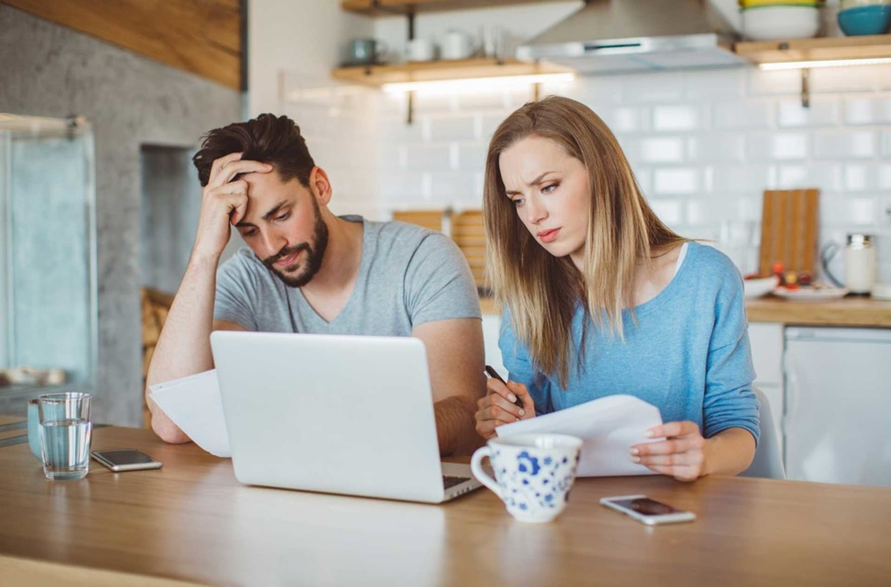 Married couple at a kitchen table looking at how much student debt is owed