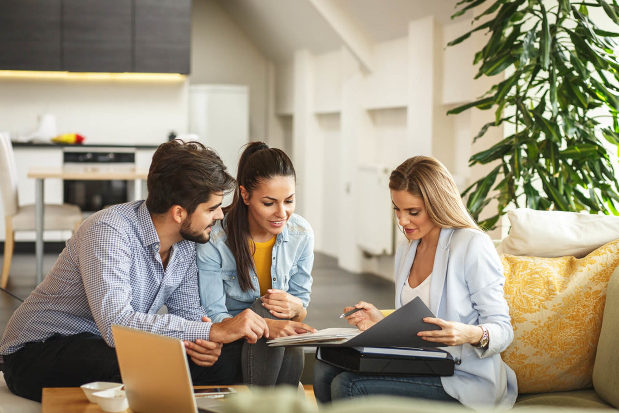 Real estate agent showing various real estate options to the home buyers