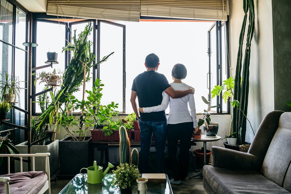 Man and woman looking out a window and talking about helping each other overcome adversity