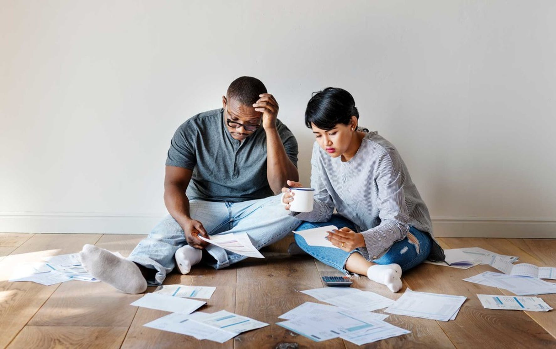 Couple sitting on the floor int heir house looking at their joint debt