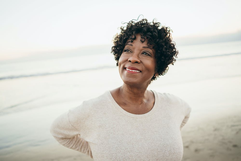 Woman on the beach thinking about how to overcome adversity