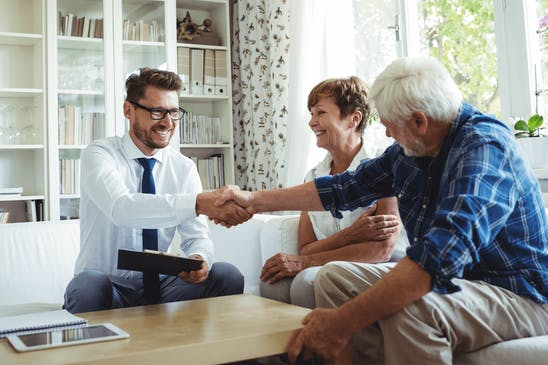 A real estate investor shaking hands with a client after buying a property subject to
