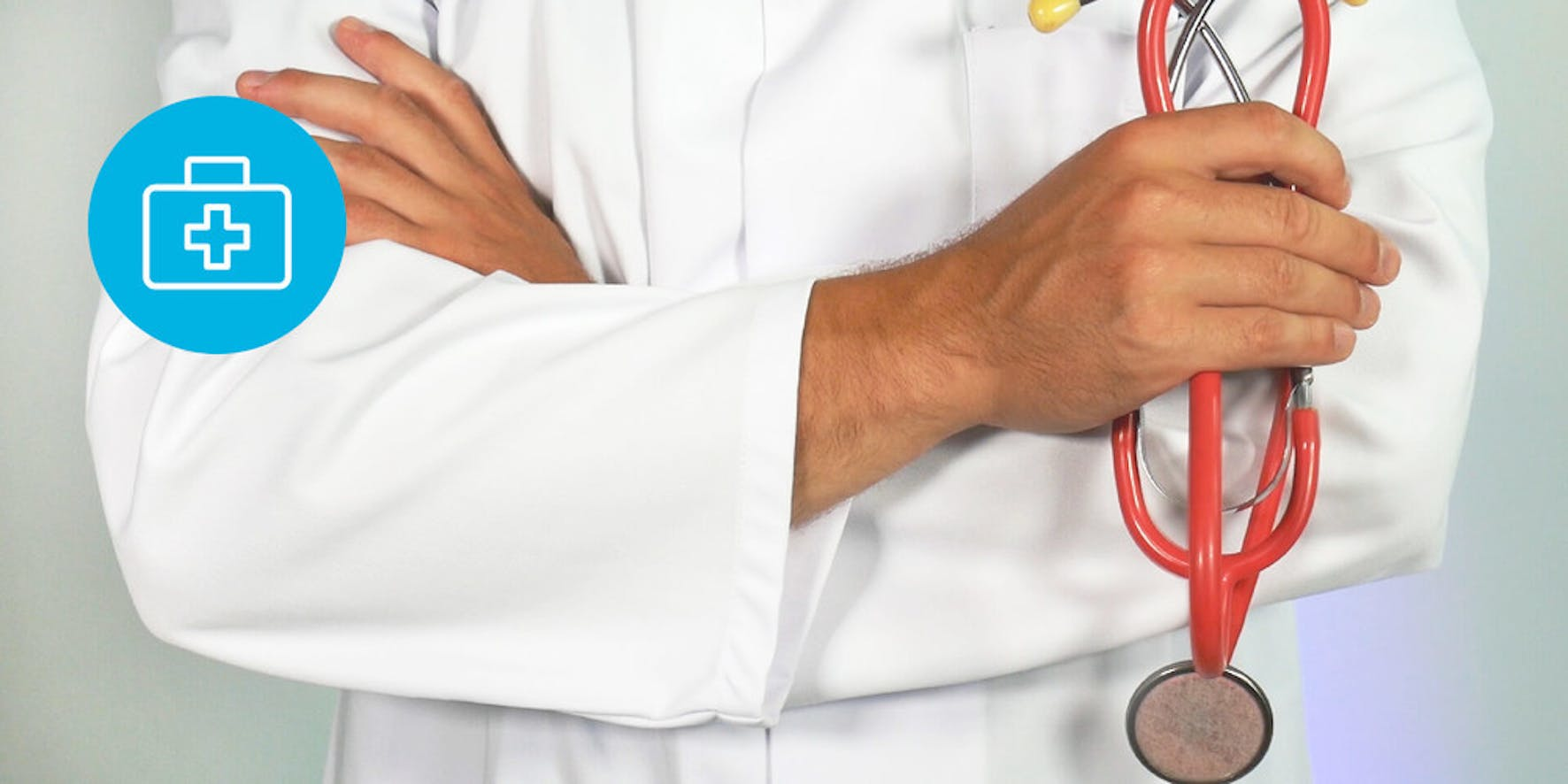 Doctor wearing a white coat and holding a red stethoscope