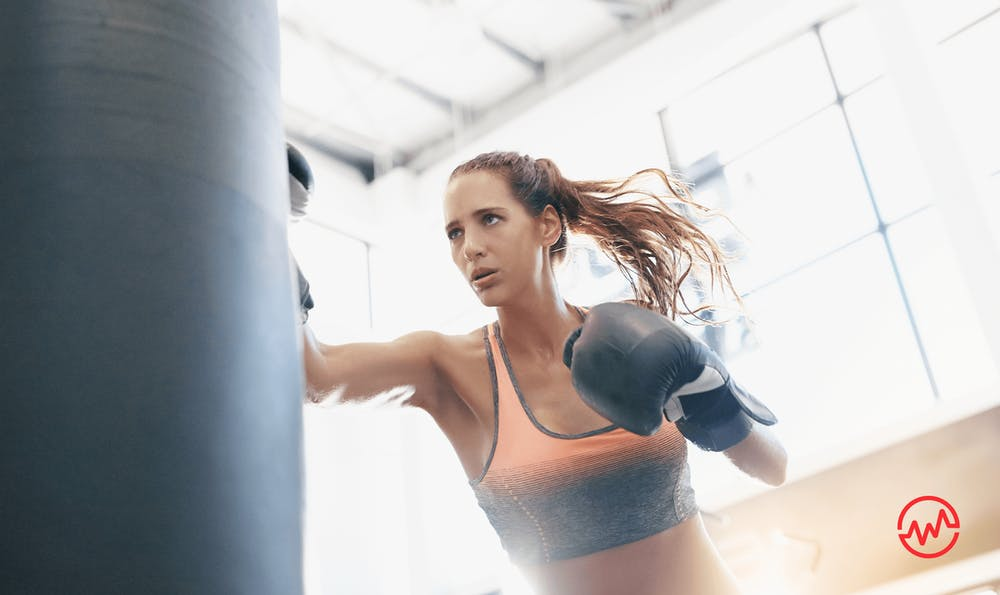 A woman hitting a boxing bag in order to stress less