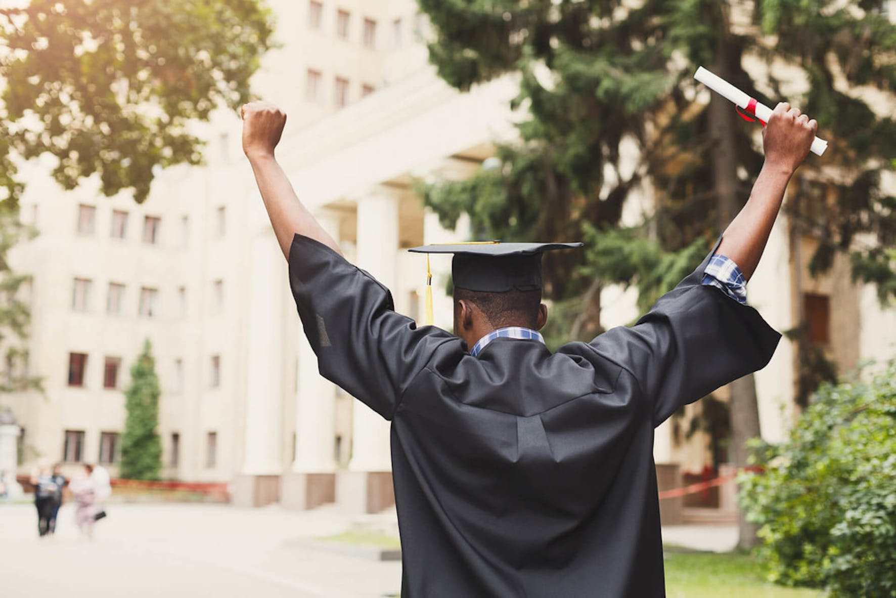 College graduate wearing a cap and gown holding his degree with his hands in the air