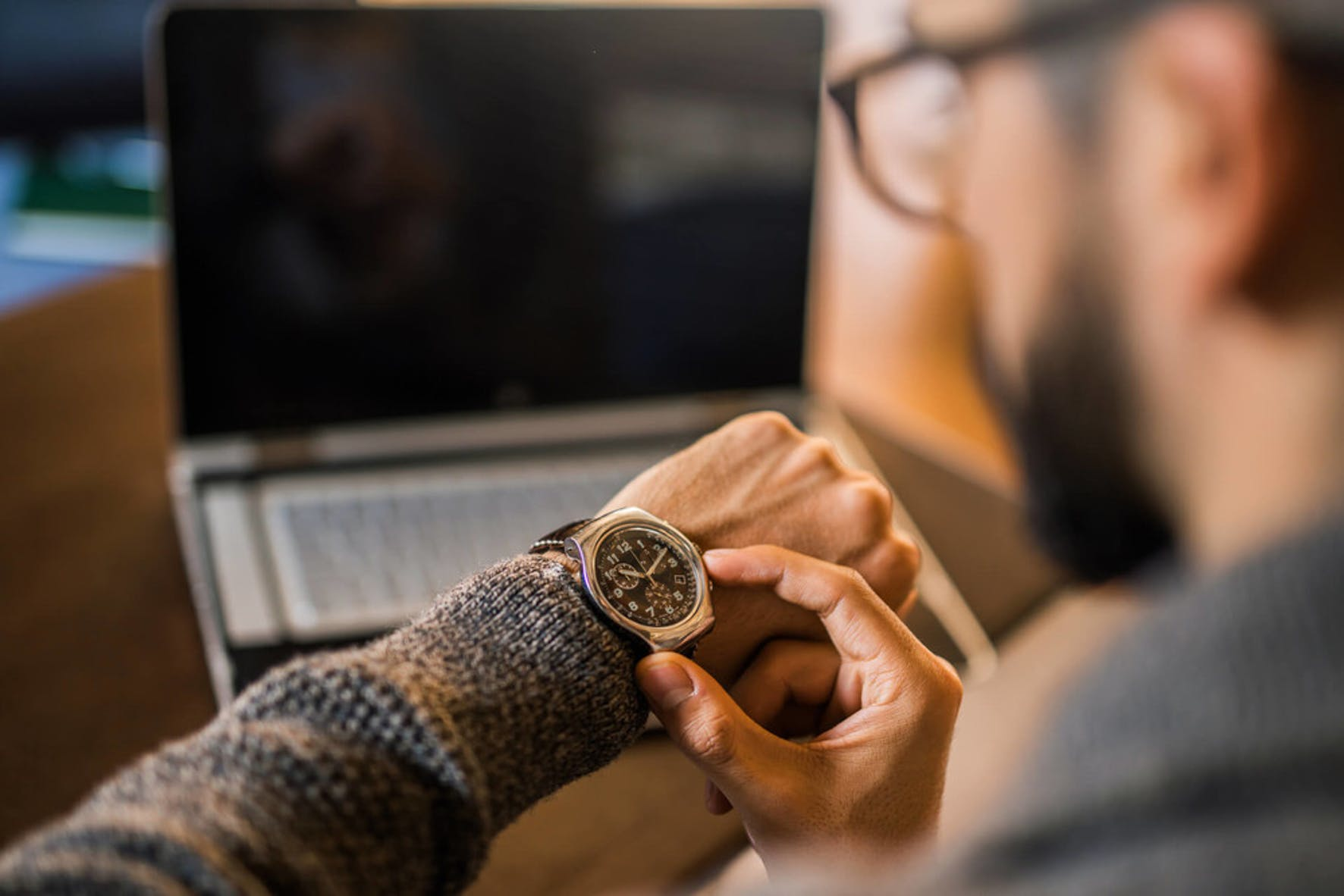 Man is looking at his watch to assess how much time he has left