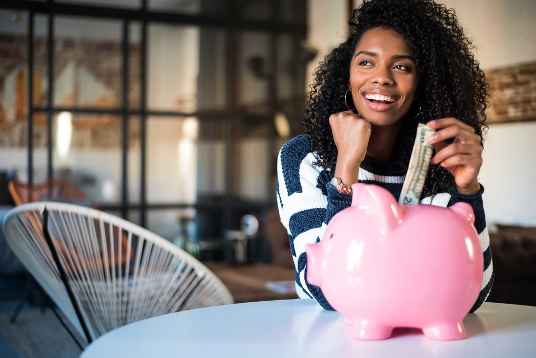 Woman saving money by putting cash in a pink piggy bank