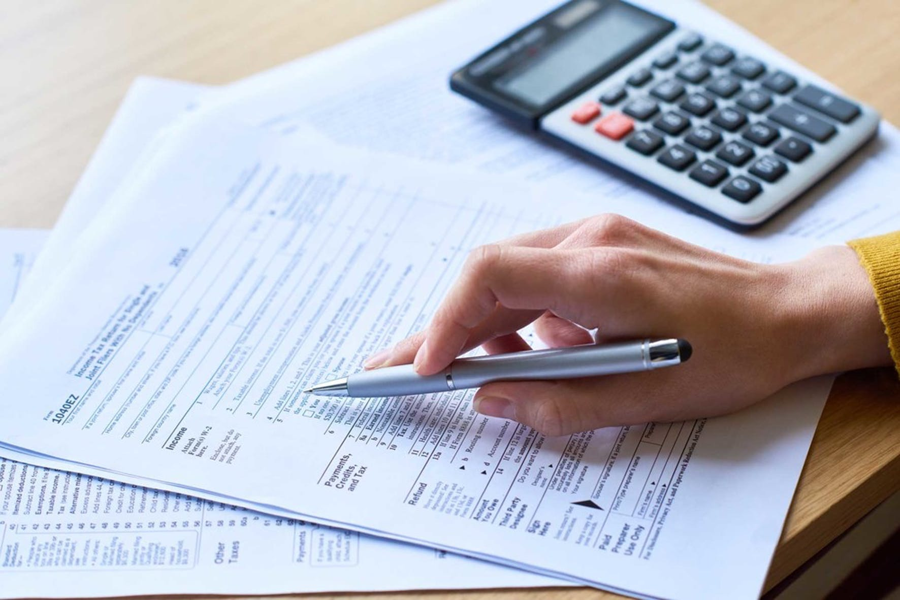 Determining how much small business tax is owed using IRS forms and a calculator