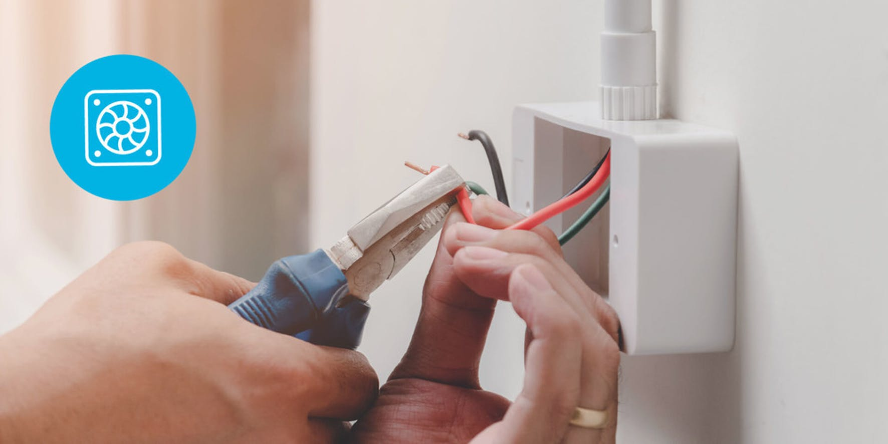 Electrician cutting a red wire inside of a wire box