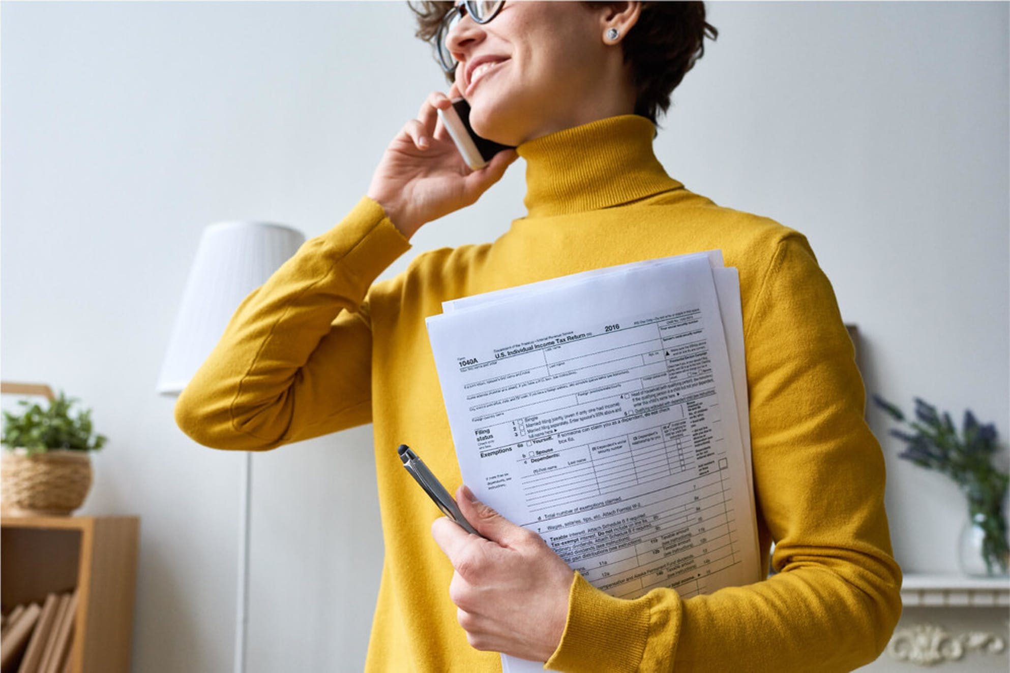Woman working on her taxes at home while talking on the phone