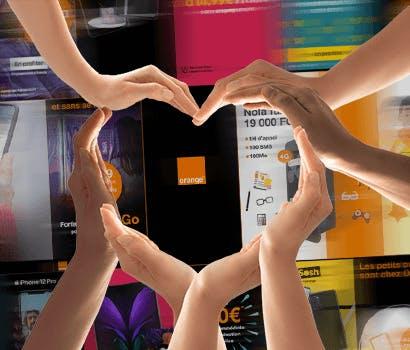 Plusieurs mains forment un coeur devant de nombreuses publicités pour l'opérateur Orange