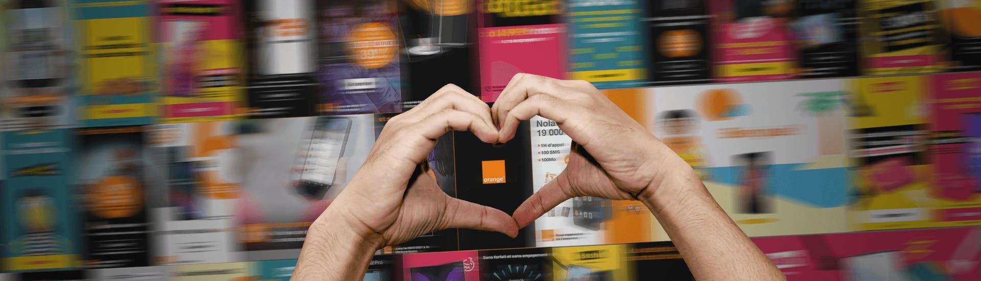Deux mains forment un coeur devant un mur de publicités digitales pour l'opérateur Orange