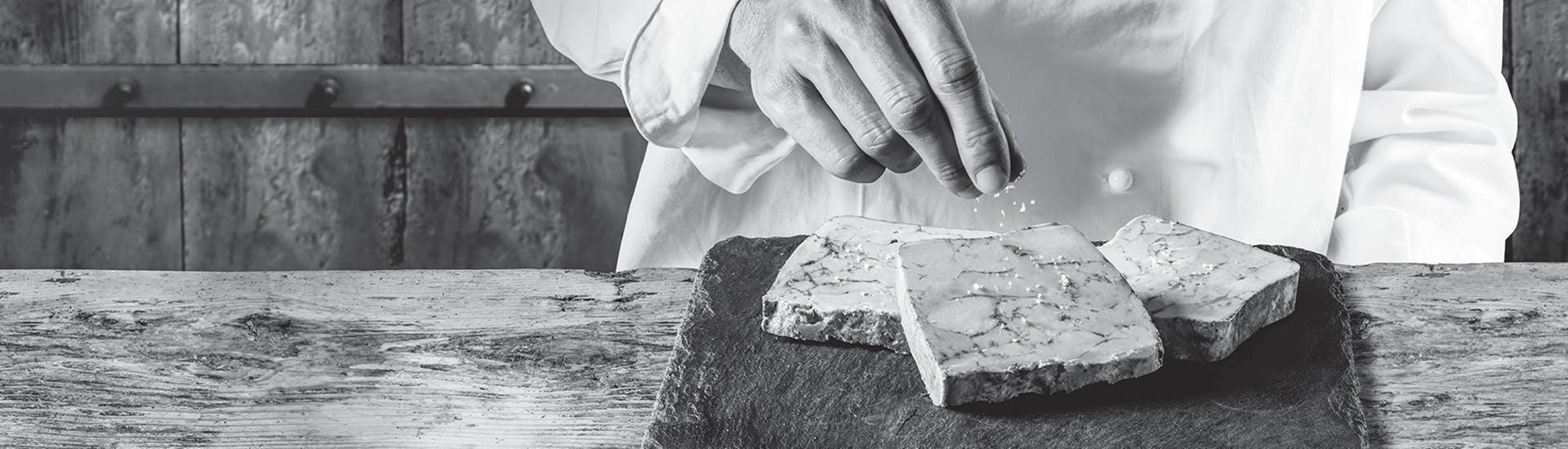 Photo en noir et blanc d'un cuisinier salant le fois gras disposé sur une ardoise posée sur une table en bois.