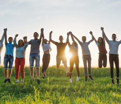 10 personnes dans un pré sautant en se tenant la main