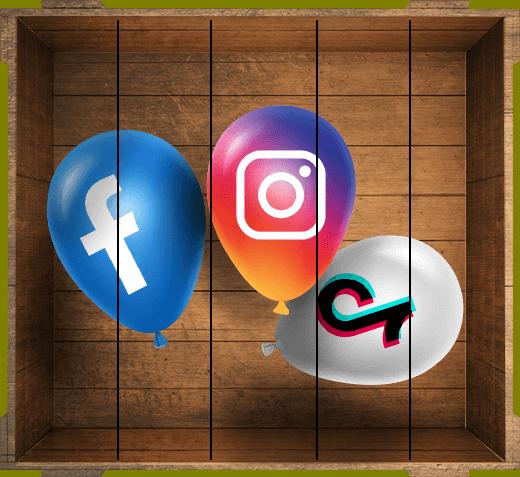 Des ballons de baudruches dans une caisse en bois. Chaque ballon a les couleurs d'un réseau sociale : Facebook, Instagram et TikTok