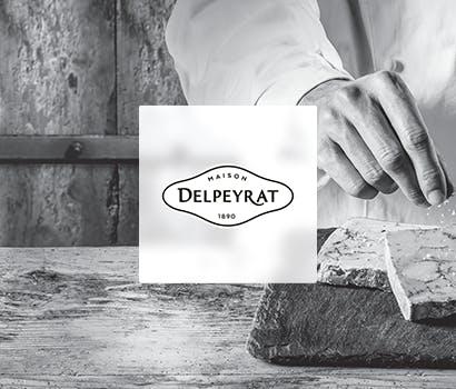 Logo Delpeyrat avec en fond une main cuisinant sur un plan de travail