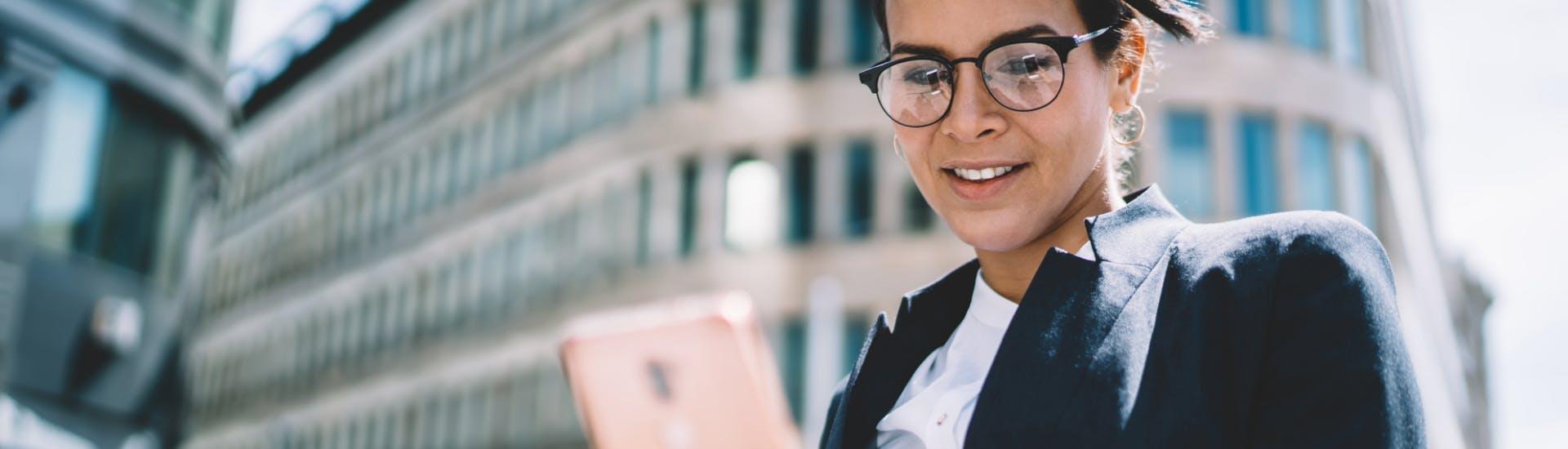 Une femme utilise l'application Visio Constat sur son smartphone pour contacter un huissier de justice.