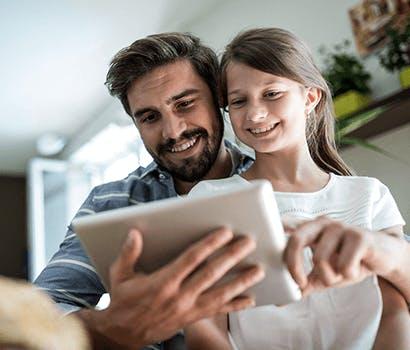 Un père et sa fille regarde une tablette connectée via Orange réseaux. Il sont en visio et sourient