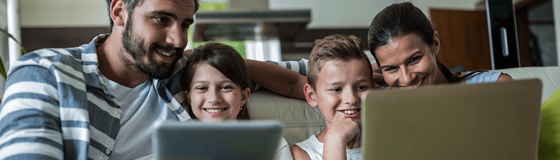 Une famille ensemble sur un canapé regarde en souriant un ordinateur portable et une tablette