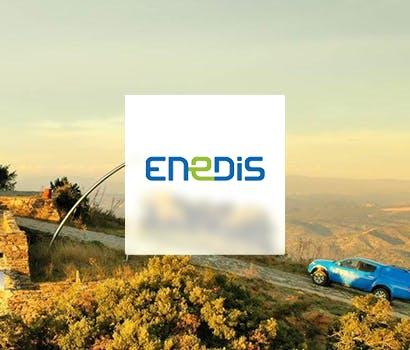 Logo Enedis avec en fond une route en terre et une voiture