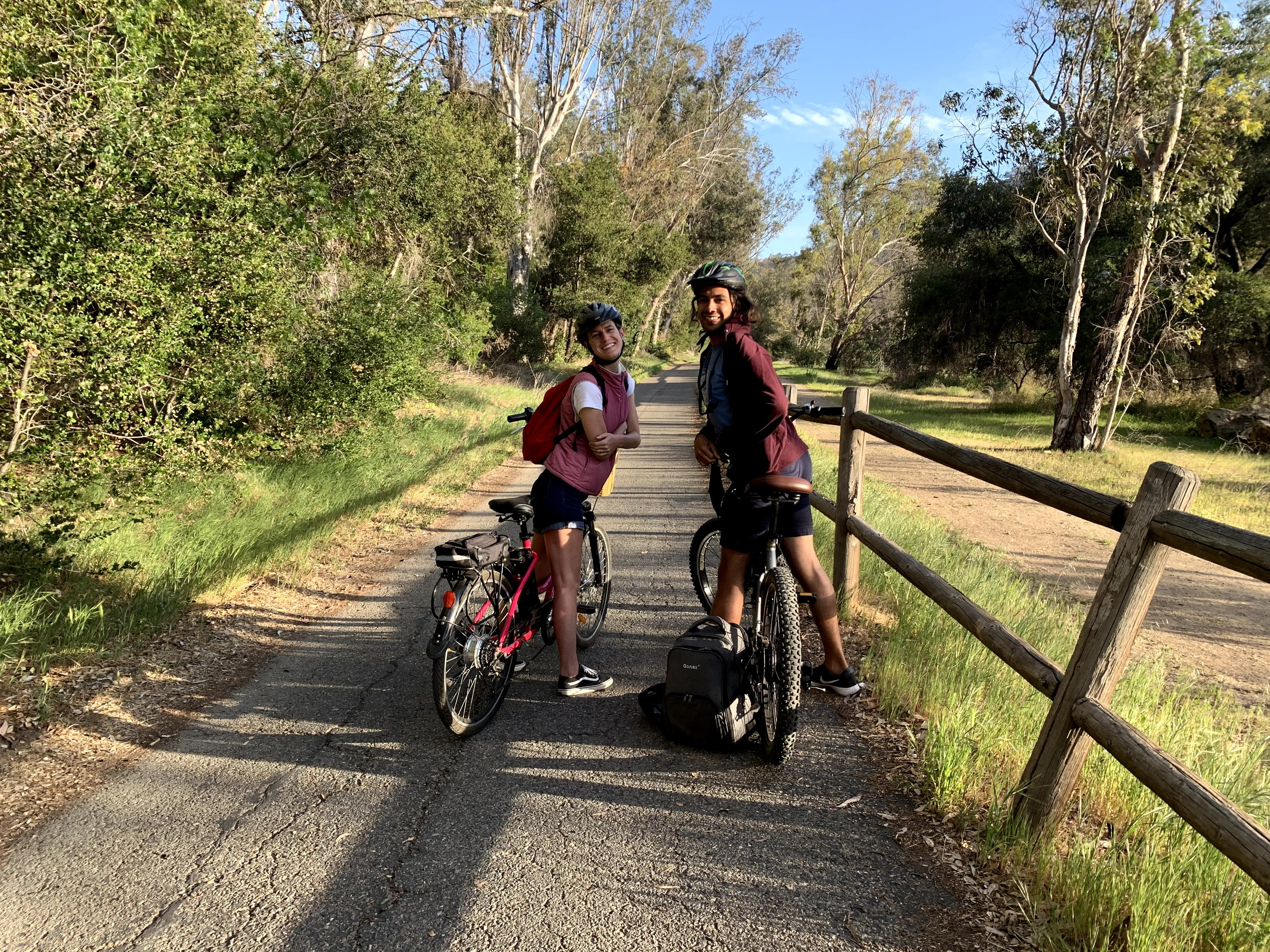 A couple on their bikes looking back to the camera smiling on the Ventura to Ojai bike path.