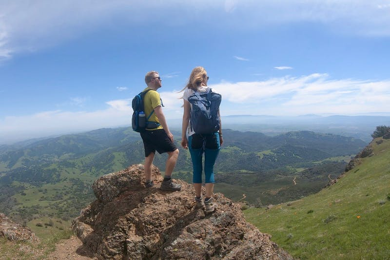 Two hikers stand on top of Mount Diablo