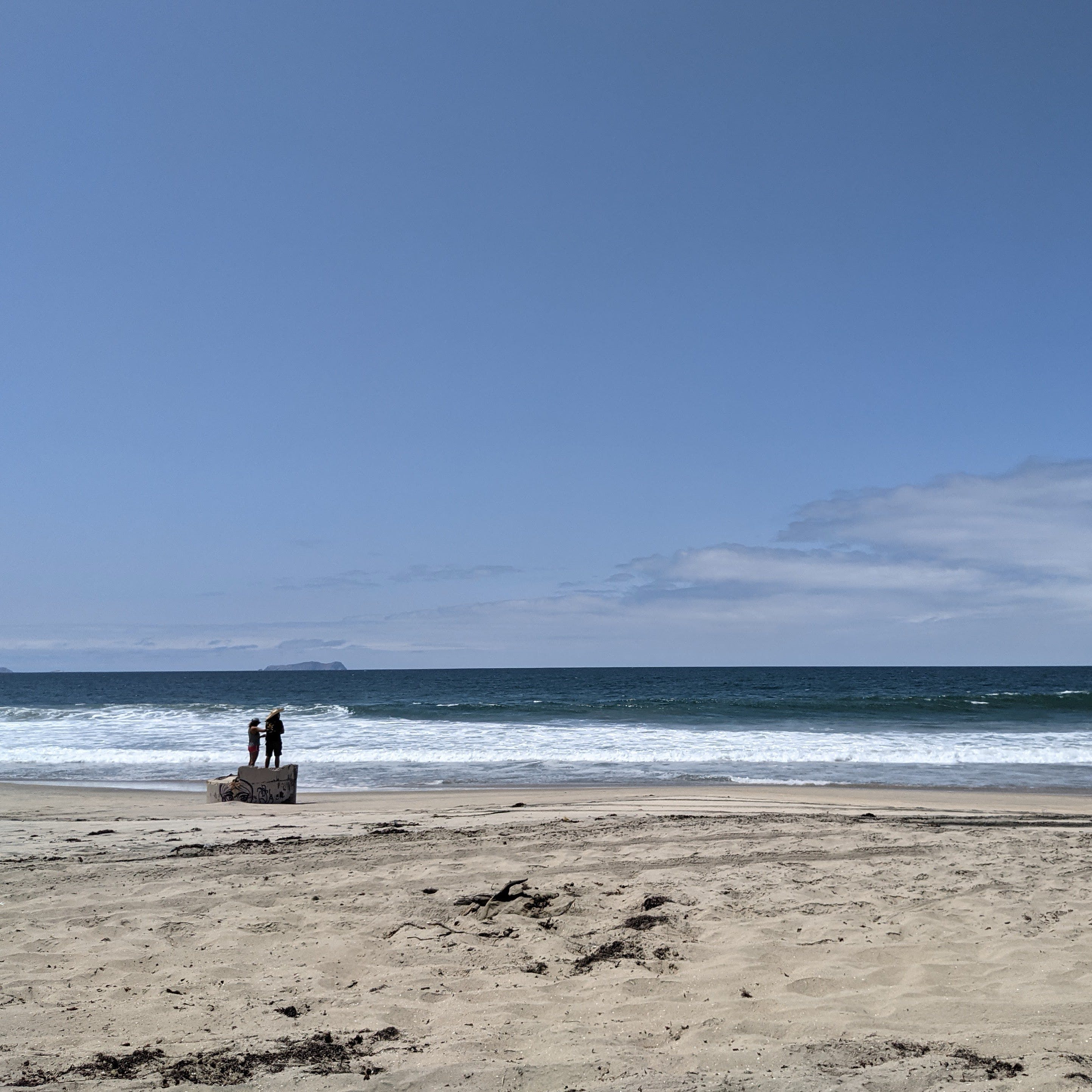 A couple stand on a concreted structure on the beach at Border Field State Park in San Diego County
