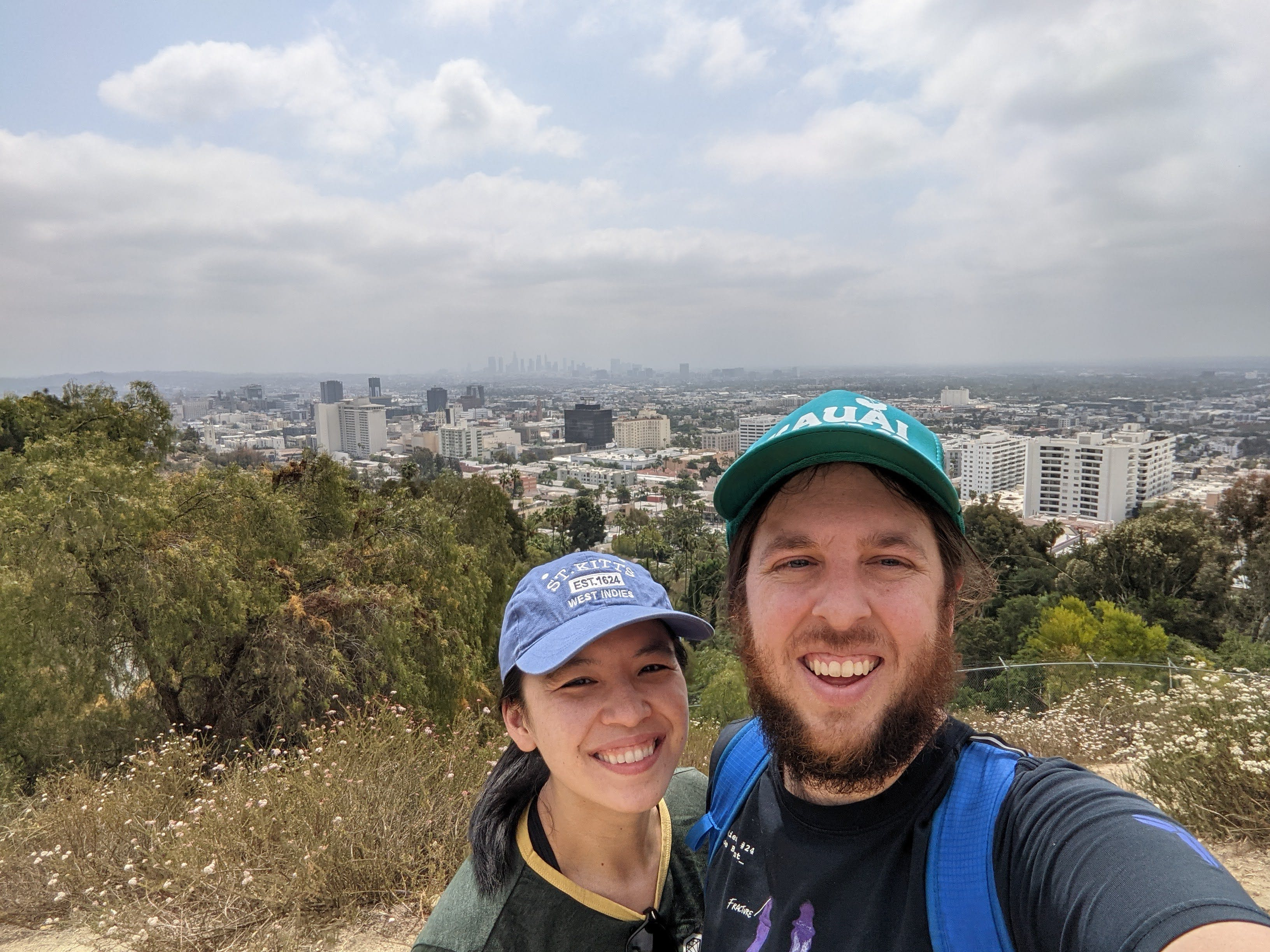 Selfie of couple on a hike at a Runyon Canyon overlook in Los Angeles overlooking the city