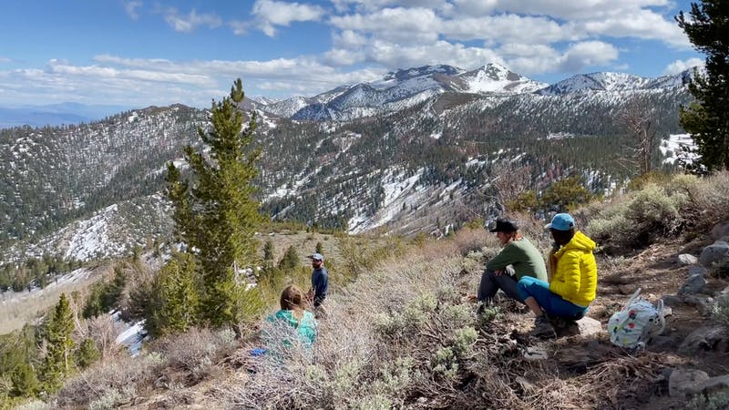 Friends sitting at a ridge overlooking Washoe Valley and Mt. Rose Wilderness mountains at Galena Creek Regional Park