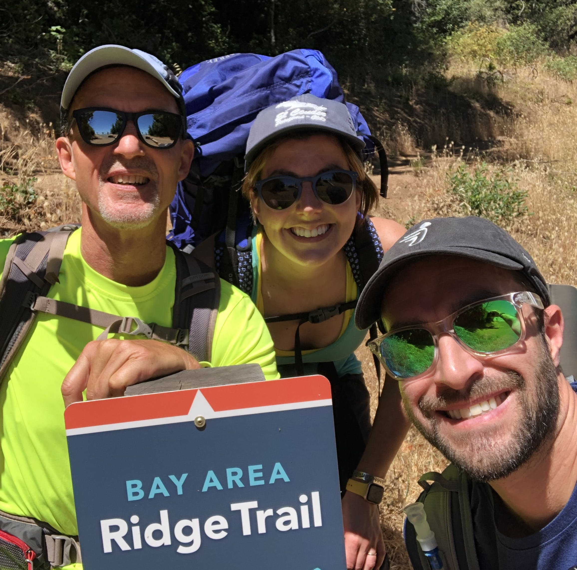 Three hikers smiling at the camera in front of the Bay Area Ridge Trail